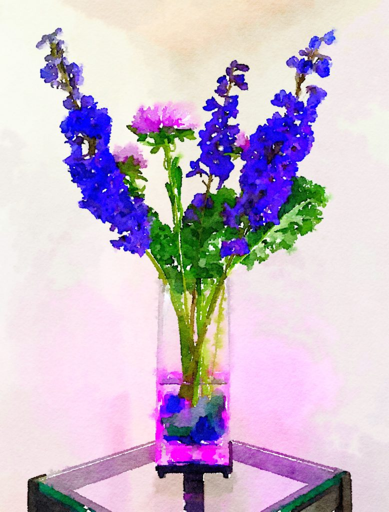 Braiden Blossoms Website Week Thirty-Three: Periwinkle Blue and Purple Flowers Over Blue Stones in a Tall Rectangular Vase